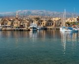 The harbor of Chania and the White Mountains behind them